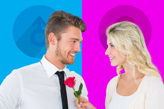 Composite image of handsome man smiling at girlfriend holding a rose Stock Photo