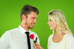 Composite image of handsome man smiling at girlfriend holding a rose Stock Image