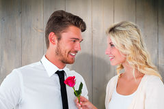 Composite image of handsome man smiling at girlfriend holding a rose Stock Images