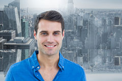 Composite image of handsome man smiling to the camera. Handsome man smiling to the camera against room with large window looking on city royalty free stock image