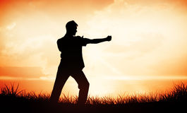 Composite image of handsome man in white doing tai chi Royalty Free Stock Photo