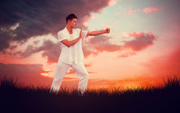 Composite image of handsome man in white doing tai chi Stock Photography