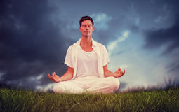 Composite image of handsome man in white meditating in lotus pose Royalty Free Stock Photography