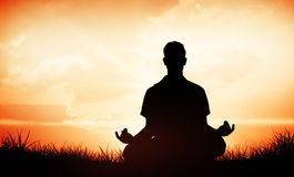 Composite image of handsome man in white meditating in lotus pose. Handsome man in white meditating in lotus pose against orange sunrise Royalty Free Stock Images