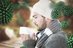 Composite image of handsome man in winter fashion blowing his nose Royalty Free Stock Photos