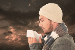 Composite image of handsome man in winter fashion blowing his nose Royalty Free Stock Images