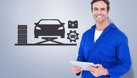 Composite image of handsome mechanic holding digital tablet Stock Photo