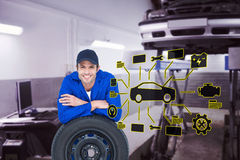 Composite image of handsome mechanic leaning on tire Stock Photos
