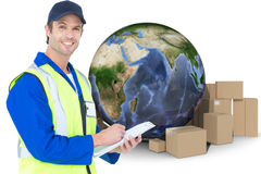 Composite image of handsome supervisor writing notes on clipboard. Handsome supervisor writing notes on clipboard against globe amidst cardboard over white Royalty Free Stock Photos