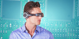 Composite image of handsome young man with virtual reality simulator Royalty Free Stock Photo