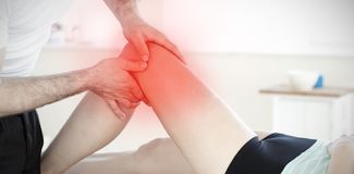 Composite image of handsome young physical therapist giving a leg massage stock images