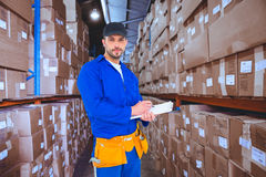 Composite image of handyman in blue overall writing on clipboard. Handyman in blue overall writing on clipboard against shelves with boxes in warehouse Royalty Free Stock Photos