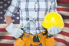 Composite image of handyman holding hammer and hard hat. Handyman holding hammer and hard hat against close-up of american flag Stock Image