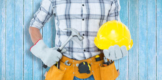 Composite image of handyman holding hammer and hard hat Royalty Free Stock Images