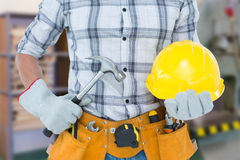 Composite image of handyman holding hammer and hard hat Stock Photo