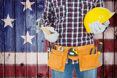 Composite image of handyman holding hard hat and hammer. Handyman holding hard hat and hammer against composite image of usa national flag Stock Images