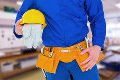 Composite image of handyman holding helmet Stock Images