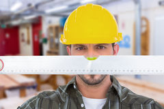 Composite image of handyman looking at spirit level Royalty Free Stock Image