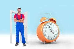 Composite image of handyman in overalls standing arms crossed over white backgound royalty free stock images