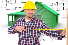 Composite image of handyman using measure tape on wooden plank Stock Images