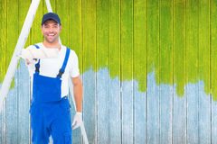 Composite image of handyman using paint roller on white background Royalty Free Stock Images