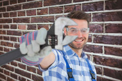 Composite image of handyman wearing protective glasses while holding wrench Royalty Free Stock Images