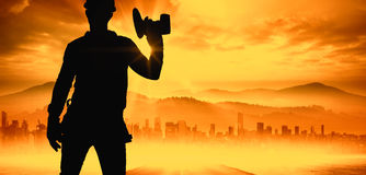 Composite image of handyman wearing tool belt while holding power drill. Handyman wearing tool belt while holding power drill against sun shining over road and stock photo