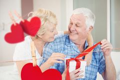 Composite image of hanging hearts and senior couple opening a gift box Stock Images