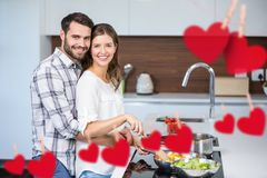 Composite image of hanging red heart and couple cooking food. In kitchen stock images