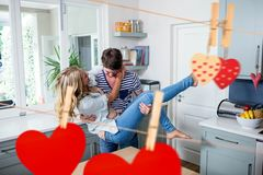 Composite image of hanging red heart and romantic couple. At home Royalty Free Stock Photography