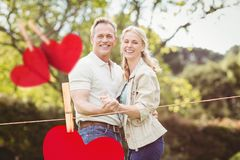 Composite image of hanging red hearts and couple embracing each other. Against park in background Royalty Free Stock Photos
