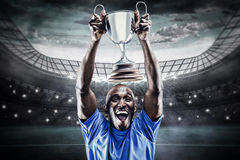 Composite image of happy athlete cheering while holding trophy Stock Photography