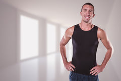 Composite image of happy athlete with hands on hip standing Royalty Free Stock Photos