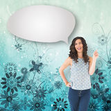 Composite image of happy beautiful brunette posing with speech bubble. Happy beautiful brunette posing with speech bubble against digitally generated girly stock images