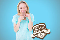 Composite image of happy blonde eating bar of chocolate. Happy blonde eating bar of chocolate against blue background with vignette stock image