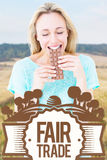 Composite image of happy blonde eating bar of chocolate. Happy blonde eating bar of chocolate against rural fields against trees and sky royalty free stock image