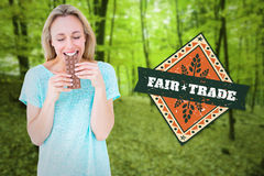 Composite image of happy blonde eating bar of chocolate. Happy blonde eating bar of chocolate against trees in the autumnal forest stock image