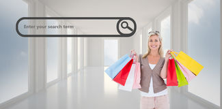 Composite image of happy blonde holding shopping bags Stock Photo