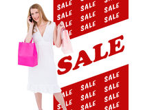 Composite image of happy blonde holding shopping bags and talking on phone Royalty Free Stock Photography