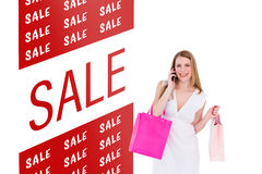Composite image of happy blonde holding shopping bags and talking on phone Royalty Free Stock Photo