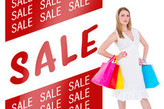 Composite image of happy blonde holding shopping bags in white dress Stock Photos