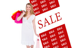 Composite image of happy blonde holding shopping bags in white dress Royalty Free Stock Photo
