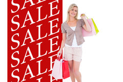 Composite image of happy blonde with shopping bags Stock Photos