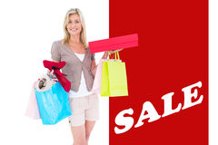 Composite image of happy blonde with shopping bags and gifts Royalty Free Stock Images
