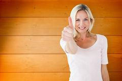 Composite image of happy blonde showing thumbs up and smiling at camera Stock Image