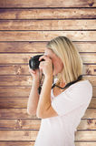 Composite image of happy blonde taking a photo on camera Royalty Free Stock Photos