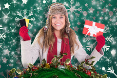 Composite image of happy blonde in winter clothes holding gifts Stock Photos