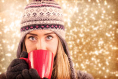 Composite image of happy blonde in winter clothes holding mug Stock Images