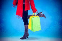 Composite image of happy blonde in winter clothes holding shopping bags. Happy blonde in winter clothes holding shopping bags against glowing christmas Royalty Free Stock Image