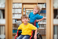 Composite image of happy boy pushing friend on wheelchair Royalty Free Stock Image